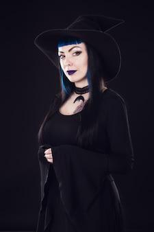 Halloweenowa czarownica z magiczną dynią. piękna młoda kobieta w czarownicach kapelusz i kostium gospodarstwa rzeźbione dyni latarnia jack. projekt sztuki halloween