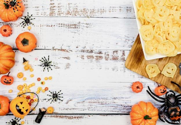 Halloweenowa dekoracja. cukierek albo psikus w okresie jesienno-jesiennym. twarz dyni i straszny symbol na tle drewna.