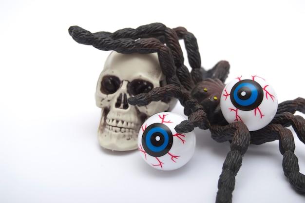 Halloweenowa dekoracja, czaszka z tarantulą na wierzchołku i dwoje oczu, odosobnionych
