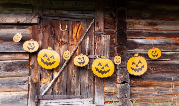 Halloweenowa dekoracja na zewnątrz. papierowa girlanda z uroczymi dyniami wisi na drewnianej ścianie starego budynku łaźni w wiosce.