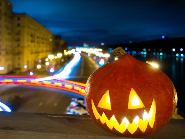 Halloweenowa dynia na tle nocnych zabudowań miasta i smugi światła od pasa...