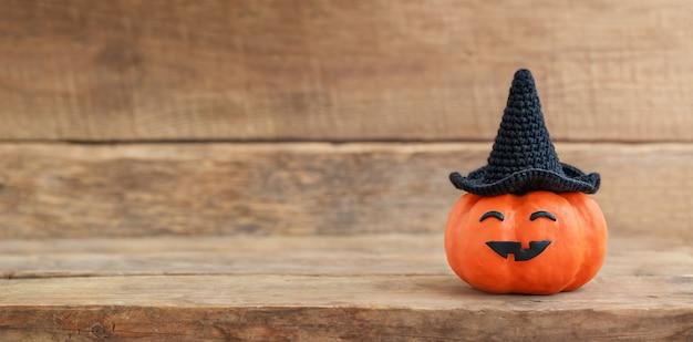 Halloweenowa dynia w czarnym kapeluszu z śmieszną twarzą na drewnianym tle
