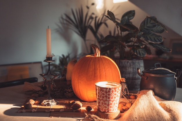 Halloweenowa dynia w stole z dekoracją szkieletowe świeczki orzechowe