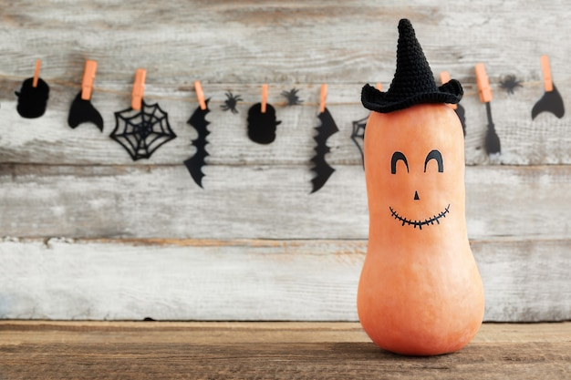 Halloweenowa dynia z śmieszną twarzą na drewnianym świątecznym tle