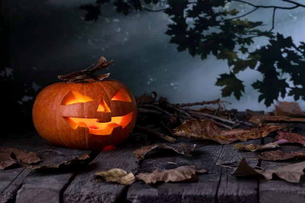 Halloweenowa dyniowa jack o lantern jarzy się w tajemniczym lesie przy nocą.