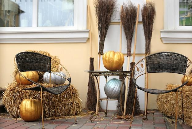 Halloweenowa instalacja plenerowa wykonana z pomalowanych na złoto i srebrze dyń wiedźmy miotły i słoma