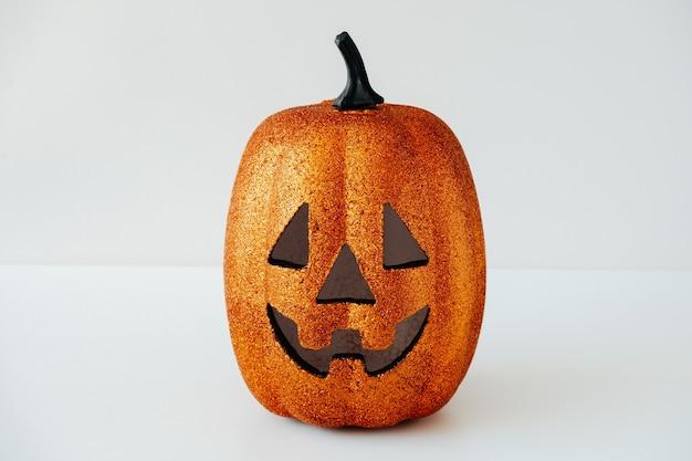Halloweenowa karta z przerażającą twarzą dyni na białym tle