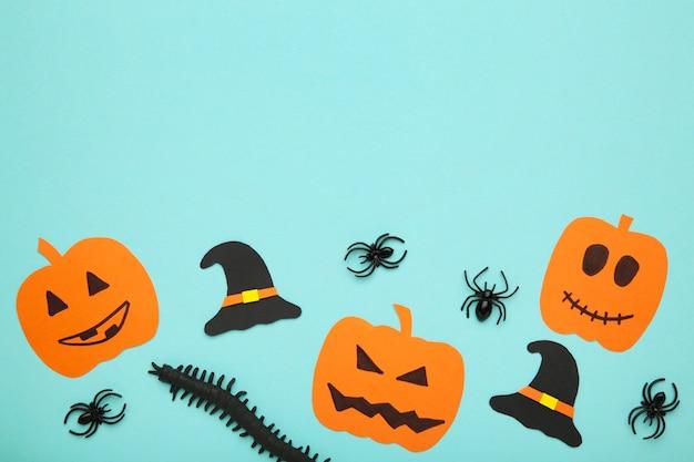 Halloweenowa kompozycja z dynią i pająkami na niebieskim tle.