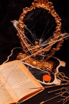 Halloweenowa kompozycja z lustrem książki i pajęczynami na czarnym tle