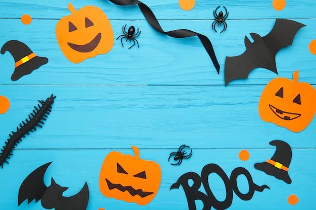 Halloweenowa kompozycja z pająkami i nietoperzami na niebieskim tle.