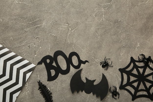 Halloweenowa kompozycja z pająkami i nietoperzami na szarym tle. widok z góry.