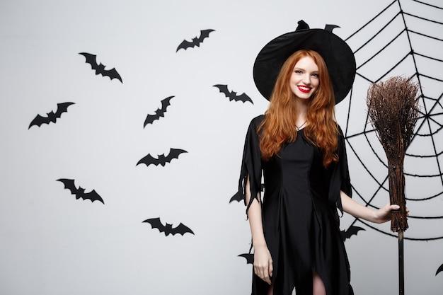 Halloweenowa koncepcja czarownicy portret pięknej młodej wiedźmy z miotłą na szarej ścianie z nietoperzem i ścianą pajęczyny