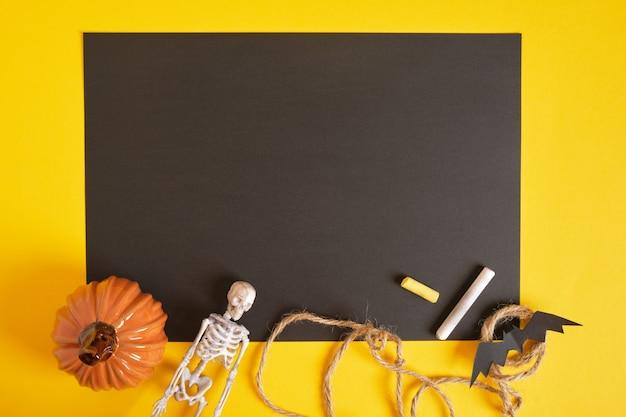 Halloweenowa makieta, pusta czarna kartka papieru i halloweenowy wystrój