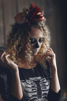 Halloweenowa makijaż czaszka piękna kobieta z blond fryzurą. modelka santa muerte w czarnym stroju.