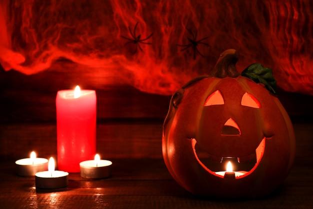 Halloweenowa pocztówka jackolatern i świece na tle pajęczyny z dwoma pająkami