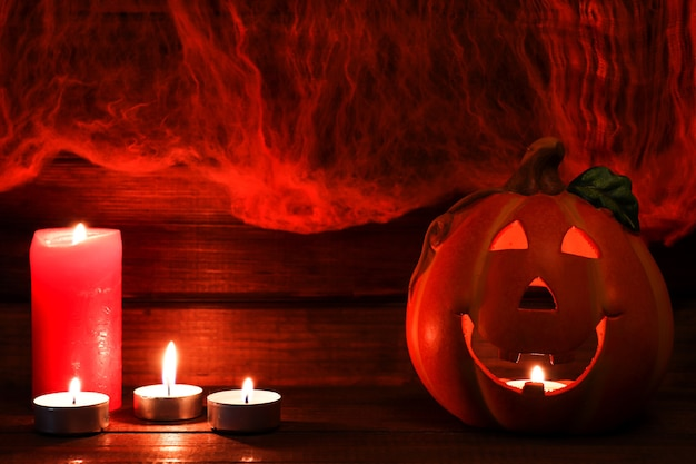 Halloweenowa pocztówka z miejscem na kopię jackolatern i świece na tle pajęczyny