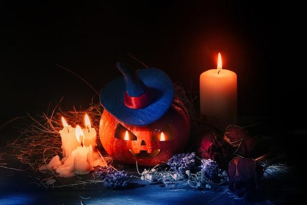 Halloweenowa pomarańczowa dynia z rzeźbioną twarzą. straszna dynia ze świecami i fioletowym kapeluszem czarownicy