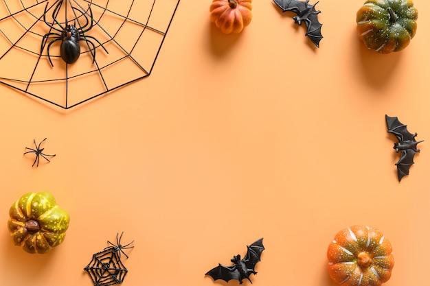 Halloweenowa ramka z zabawnymi dekoracjami na przyjęcie, dynie, słomka, nietoperz, czaszki, straszny pająk na pomarańczowym tle. widok z góry, płaski układ. skopiuj miejsce.