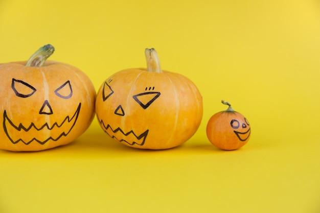 Halloweenowa rodzina dyniowa z przerażającymi złymi twarzami na żółtym tle koncepcja rodzice i dzieci tem...