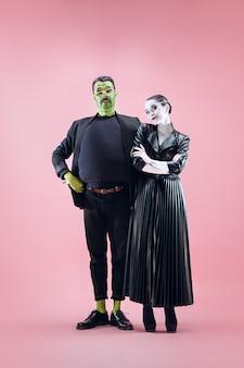 Halloweenowa rodzina. szczęśliwa para w halloween kostium i makijaż. krwawy motyw: szalone twarze maniaków na różowym tle studia