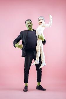 Halloweenowa rodzina. szczęśliwy ojciec i dzieci dziewczyna w kostium na halloween i makijaż. krwawy motyw: szalone twarze maniaków na różowym tle studia