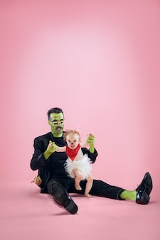 Halloweenowa rodzina. szczęśliwy ojciec i dzieci noworodka dziewczyna w kostium na halloween i makijaż. krwawy motyw: szalony maniak na różowym tle studia