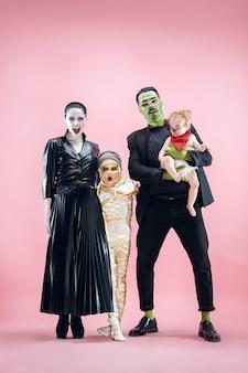 Halloweenowa rodzina. szczęśliwy ojciec, matka i dzieci dziewczyny w halloween kostium i makijaż. krwawy motyw: szalone twarze maniaków na różowym tle studia
