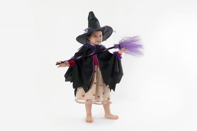 Halloweenowa śliczna dziewczyna jest ubranym czarownica kostium na bielu