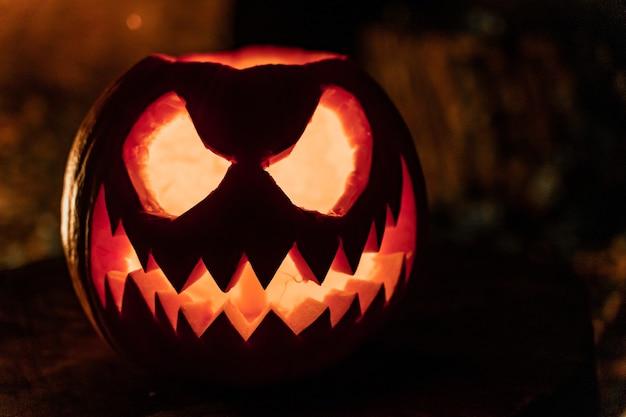 Halloweenowa twarz dyni z zapalonymi świecami i ogniskiem w tle upiorna twarz i ogień w stawie