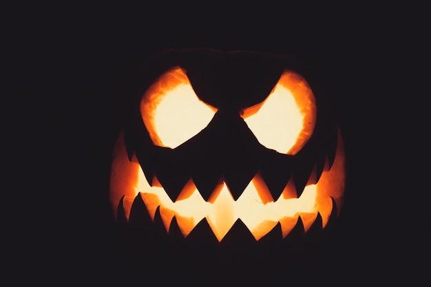 Halloweenowa twarz dyni ze świecą zapaloną na czarnym tle upiorna twarz