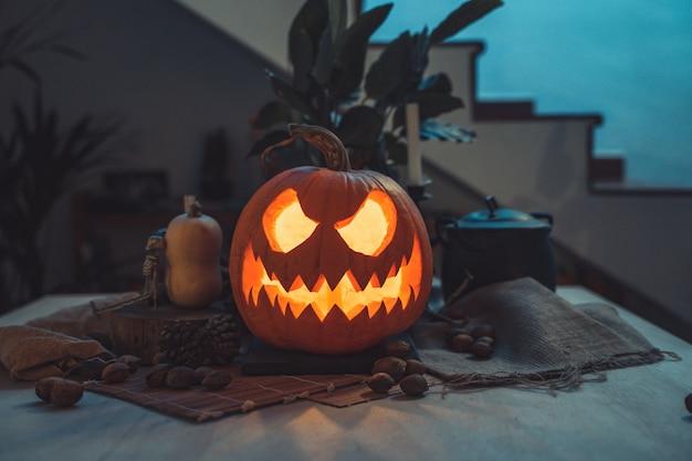 Halloweenowa upiorna twarz dyni w stole z dekoracją szkieletowe świece orzechy