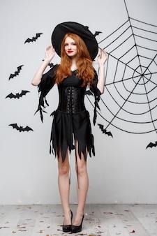 Halloweenowa Wiedźma Koncepcja Pełnej Długości Szczęśliwego Halloween Wiedźma Trzymająca Pozowanie Nad Ciemnoszarą ścianą Z Nietoperzem I Pajęczyną Darmowe Zdjęcia