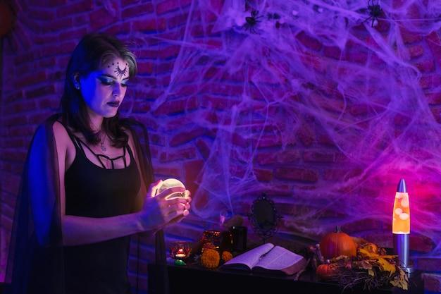 Halloweenowa wiedźma, młoda kobieta przebrana za wiccę trzymająca magiczną kulę nad pajęczyną