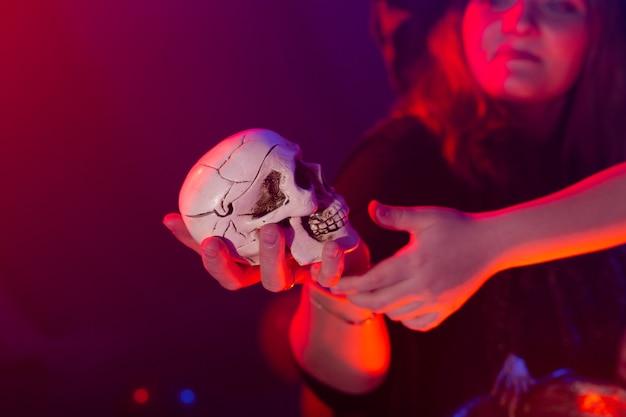Halloweenowa wiedźma robiąca magię z czaszką w halloweenowych nocnych magicznych wakacjach i mistycznej koncepcji