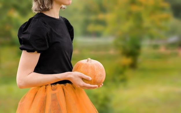 Halloweenowa wiedźma trzymająca dynię w dłoniach