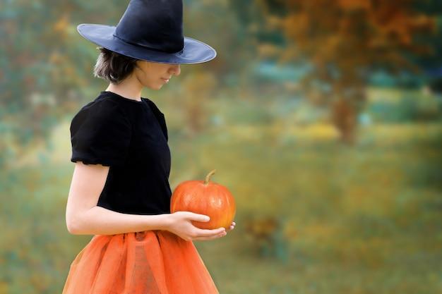 Halloweenowa wiedźma w czarnym kapeluszu trzymająca dynię w dłoniach