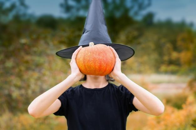Halloweenowa wiedźma w czarnym kapeluszu trzymająca dynię zamiast głowy