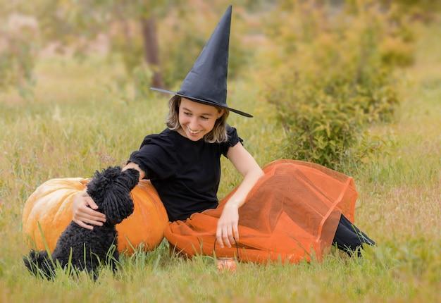 Halloweenowa wiedźma z czarnym psem