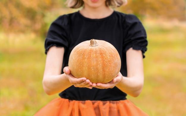Halloweenowa wiedźma z dynią w dłoniach