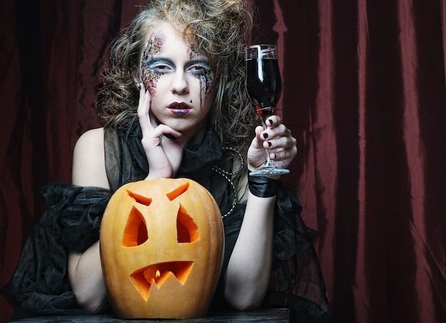 Halloweenowa wiedźma z rzeźbioną dynią na czerwonym dywanie
