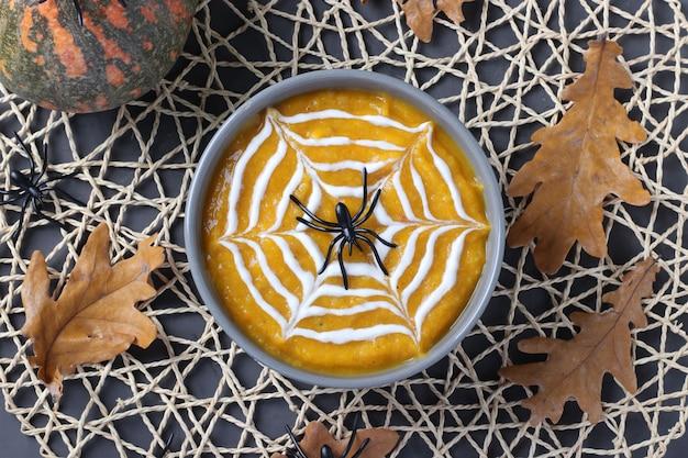 Halloweenowa zupa dyniowa z kremową pajęczyną w szarej misce i pająkami na stole. widok z góry.