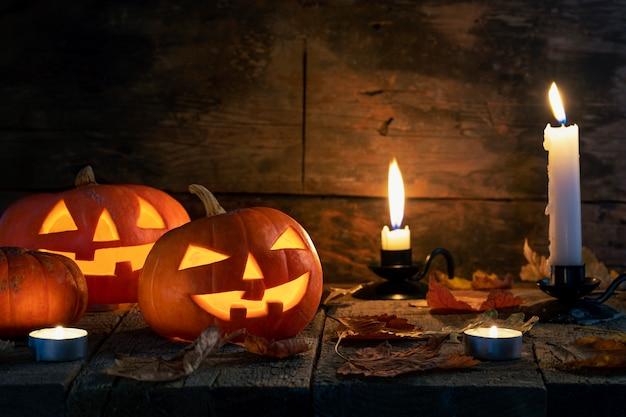 Halloweenowe banie przewodzą jack o lampion na drewnianym stole.