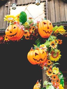 Halloweenowe banie z jesień kwiatami i dekoracjami na zewnątrz domu. rodzinna zabawa, rzeźbione dynie w jack-o-lanterns na halloween