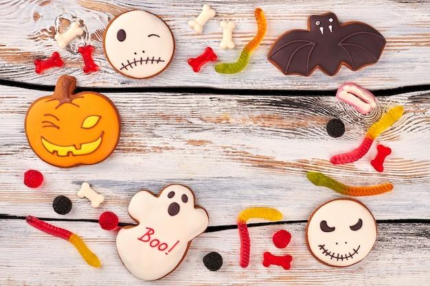 Halloweenowe ciasteczka i cukierki na drewnianym tle.