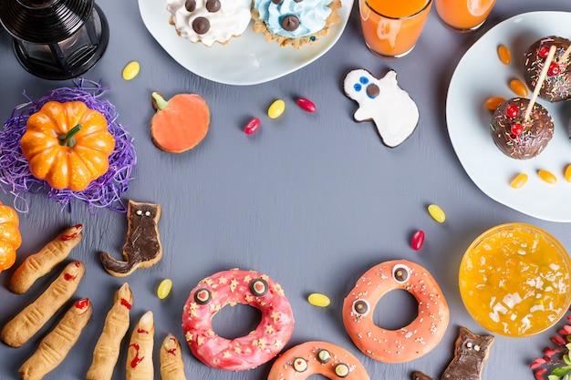Halloweenowe ciasteczka i inne słodkie smakołyki na stole