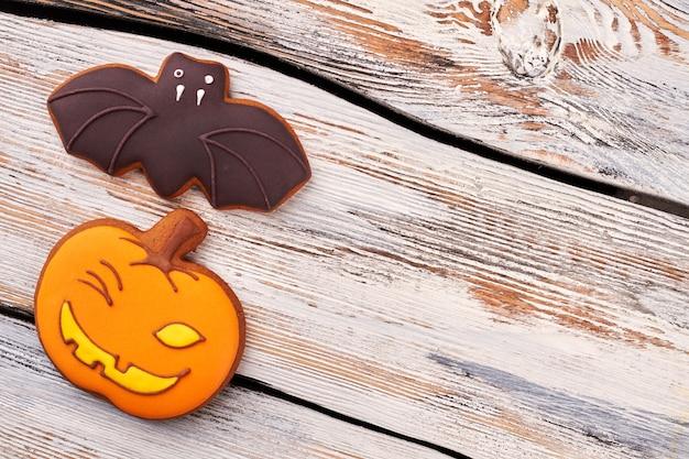 Halloweenowe cukrowe ciasteczka na drewnianym tle.