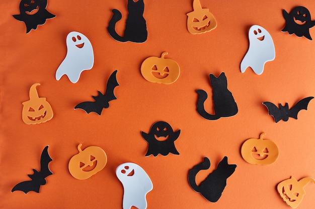 Halloweenowe dekoracje, dynie, nietoperze i duchy na pomarańczowym tle