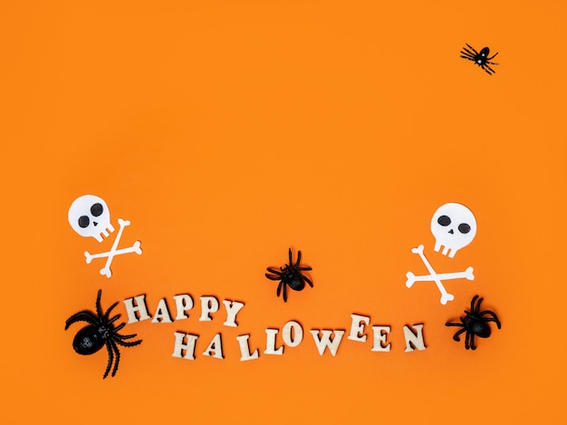Halloweenowe dekoracje na pomarańczowym tle z napisem happy halloween i pająki
