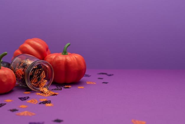 Halloweenowe dynie dekoracyjne na fioletowym tle z miejsca na kopię. dynie i konfetti w postaci pająków i pajęczyn.