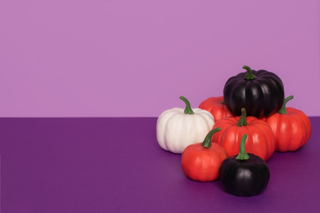 Halloweenowe dynie dekoracyjne na fioletowym tle z miejsca na kopię. dynie pomalowane na czarno, biało i pomarańczowo.
